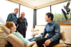 Business Photos - Dr. Tom Zyvolovski discussing dental options with a family.